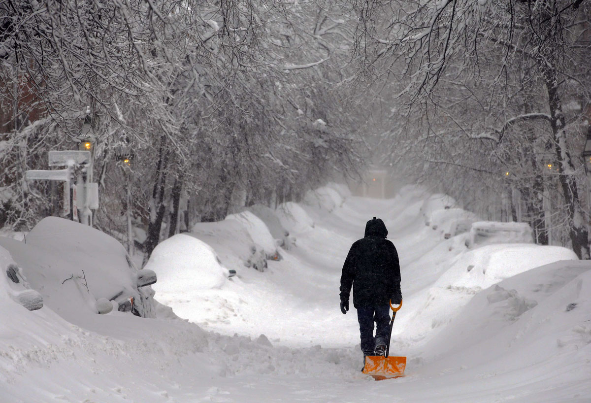 Man walking with snow shovel on Boston road during winter storm of 2015.