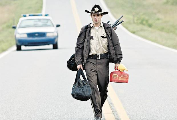 rick grimes carrying guns and kerosene walking alone down the highway